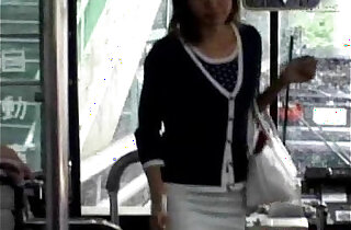 A young girl enters a public bus and sits down from